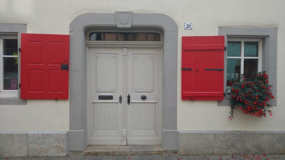 Eine grauumrandete Tür und Fenster, umgeben von roten Fensterläden. Auf einem Fenstersims steht eine rotblühende Pflanze.